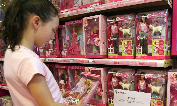 A young girl holds a Barbie doll next to a notice saying that the toy 'Barbie and Tanner' made by US toy giant Mattel, which has just been recalled in the US, is out of stock at a Toys 'R' Us store in Shanghai, 15 August 2007. (MARK RALSTON/AFP/Getty Images)