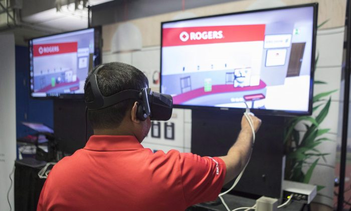 A Rogers employee wears virtual reality (VR) goggles at a stall promoting VR retail over 5G wireless networks, at a press event in Toronto on April 16, 2018. Rogers Communications announced that it expects to test new high-speed 5G networks in selected cities across Canada in 2019. (The Canadian Press/Chris Young)