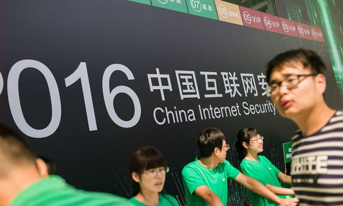 Chinese volunteers wait for attendees at the China Internet Security Conference in Beijing on Aug. 16, 2016. (Fred Dufour/AFP/Getty Images)