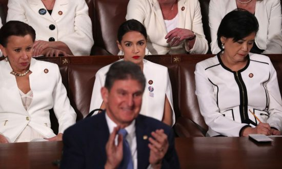 DDemocratic women of the House of Representatives, including Rep. Alexandria Ocasio-Cortez (D-N.Y.) (C), remain seated as Senator Joe Manchin (D-W. Va.) stands and applauds in front of them during President Donald Trump's State of the Union address in Washington on Feb. 5, 2019. (Jonathan Ernst/Reuters)