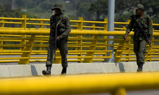 Venezuelan military forces stand guard as they block with containers the Tienditas Bridge, which links Tachira, Venezuela, and Cucuta, Colombia, on Feb. 6, 2019. (RAUL ARBOLEDA/AFP/Getty Images)
