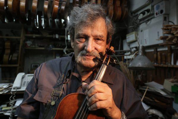 Israeli violin maker Amnon Weinstein holds a violin