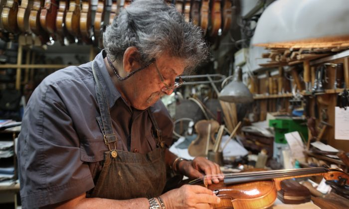 """Israeli violin maker Amnon Weinstein restores a violin which he named the """"Auschwitz Violin"""" since it belonged to a Jewish man imprisoned at the Auschwitz concentration camp during the Second World war at his workshop in Tel Aviv on July 15, 2016. (Menahem Kahana/AFP/Getty Images)"""