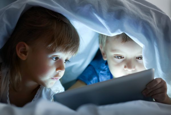 children lying under blanket with tablet