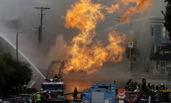 San Francisco firefighters battle a fire on Geary Boulevard in San Francisco, Wednesday, Feb. 6, 2019. (AP Photo/Jeff Chiu)