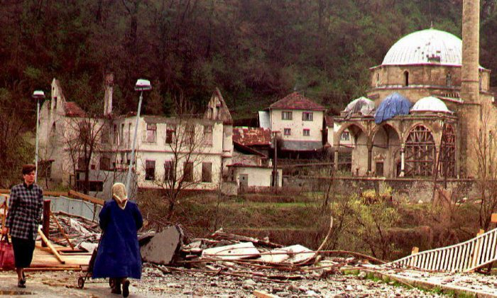 Two women pass a bridge, damaged by Serb artillery fire, to cross the Bosna river 27 March 1994. At right, the half-destroyed mosque of Maglaj. The siege of this mainly Moslem enclave was lifted last week. (Photo credit should read ERIC CABANIS/AFP/Getty Images)