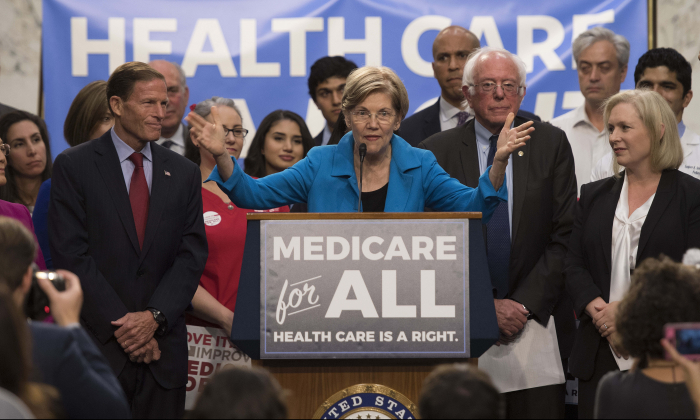Sen. Elizabeth Warren (C), a Democrat from Massachusetts, speaks with Sen. Bernie Sanders (2nd R), an Independent from Vermont, as they discusses Medicare for All legislation on Capitol Hill in Washington, on Sept. 13, 2017. (Jim Watson/AFP/Getty Images)