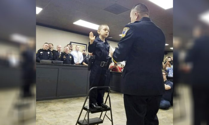 In this Feb. 7, 2019 photo provided by the Freeport Police Department, 6-year-old Abigail Arias, who is battling cancer, is sworn in as a Texas police officer by Freeport Police Chief Ray Garivey in Freeport, Texas. (Freeport Police Department via AP)