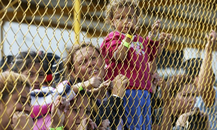 Central American immigrant families look out through the fence of a shelter in Piedras Negras, Mexico, on Feb. 5, 2019. (Jerry Lara/The San Antonio Express-News via AP)