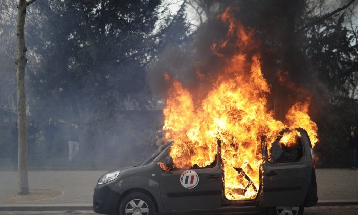 A burning command car belonging to France's anti-terror 'Vigipirate' squad, dubbed 'Operation Sentinelle', is pictured during a demonstration as yellow vests protesters keep pressure on French President Emmanuel Macron's government, for the 13th straight weekend of demonstrations, in Paris, France, on Feb. 9, 2019. (Kamil Zihnioglu/AP Photo)