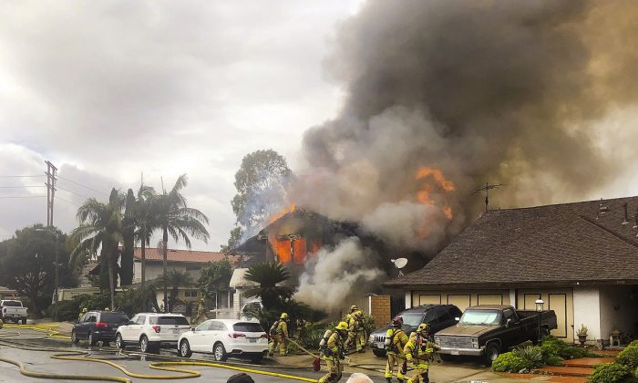 Yorba Linda firefighters rush to a home engulfed in flames after a deadly small plane crash in Yorba Linda, Calif. on Feb. 3, 2019. (Kyle Vanderheide via AP, File)