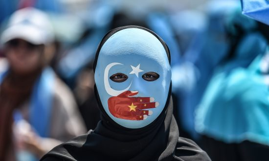 A demonstrator wearing a mask painted with the colors of the flag of East Turkestan—how some separatist Uyghurs refer to the region of Xinjiang—and a hand bearing the colors of the Chinese flag, attends a protest denouncing China's treatment of ethnic Uyghur Muslims, in front of the Chinese consulate in Istanbul, on July 5, 2018. (OZAN KOSE/AFP/Getty Images)