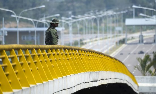 A Venezuelan military officer stands guard as containers block the Tienditas Bridge, which links Tachira, Venezuela, and Cucuta, Colombia, on Feb. 6, 2019. (RAUL ARBOLEDA/AFP/Getty Images)