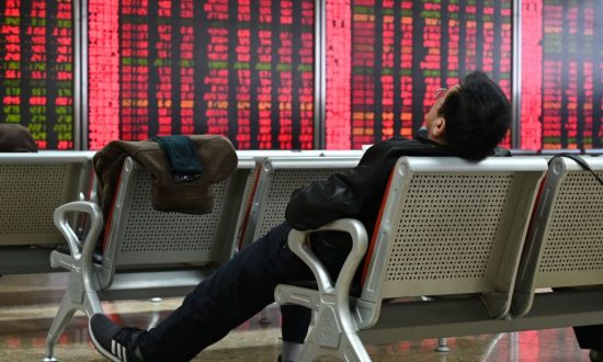 A man rests in front of screens showing stock prices at a securities company in Beijing on Jan. 21, 2019. (Greg Baker/AFP/Getty Image)