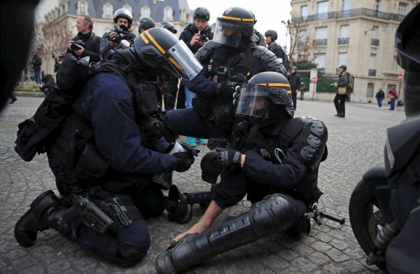 An injured policeman in riot gear is given help