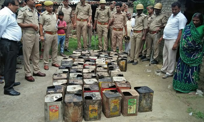 Indian police gather around containers of bootleg alcohol recovered in a raid after multiple deaths from alcohol poisoning in Azamgarh Village in Uttar Pradesh State on July 11, 2017. (STR/AFP/Getty Images)