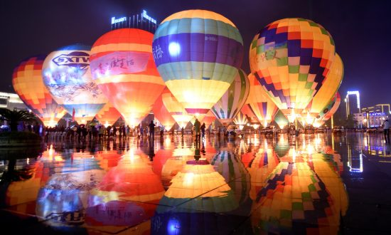 People look at hot air balloons decorating a plaza, during a tourism event in Qianxinan Buyei and Miao Autonomous Prefecture, Guizhou Province, China on Oc. 14, 2018. (China Daily via Reuters)