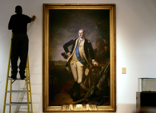 worker on ladder by painting of George Washington