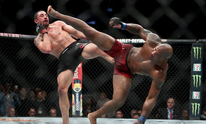 Robert Whittaker of New Zealand (L) and Yoel Romero of Cuba (R) each attempt a kick in the fifth round in their middleweight title fight during the UFC 225: Whittaker v Romero 2 event at the United Center on Jun. 9, 2018 in Chicago, Ill. (Dylan Buell/Getty Images)