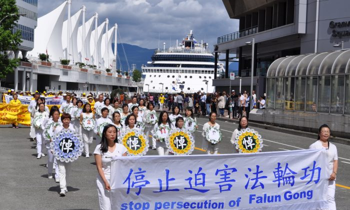 A procession of Falun Dafa adherents in white hold memorial wreaths to pay tribute to their fellow practitioners who have died due to torture and persecution in China during a parade in downtown Vancouver on July 16, 2017. (Tang Feng/The Epoch Times)