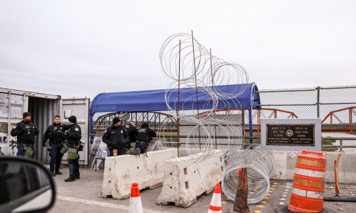 U.S. Customs and Border Protection officers stand next to newly-installed concertina wire halfway along the Camino Real International Bridge from Piedras Negras, Mexico, towards Eagle Pass, Texas, on Feb. 8, 2019. (Charlotte Cuthbertson/The Epoch Times)