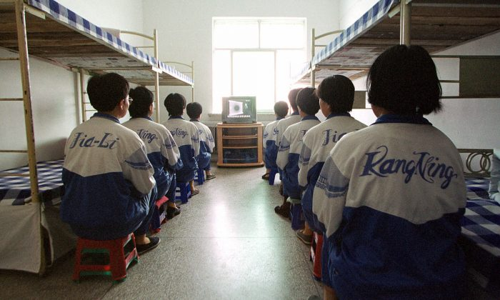 """Falun Dafa practitioners are shown in Masanjia labour camp watching a video meant to """"re-educate"""" them during a propaganda tour arranged by the camp authorities on May 22, 2001. One of the tortures used on the practitioners involves handcuffing them awkwardly between bunk beds, and then yanking the beds apart, causing excruciating pain. (AP Photo/John Leicester)"""