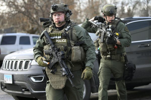 Police officers armed with rifles gather at the scene