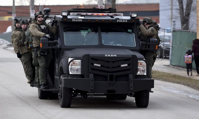 Police officers ride on a vehicle near the site of a shooting at a manufacturing plant in Aurora, Ill., that police said left several people dead, and several police officers wounded, on Feb. 15, 2019. (Matt Marton/AP Photo)