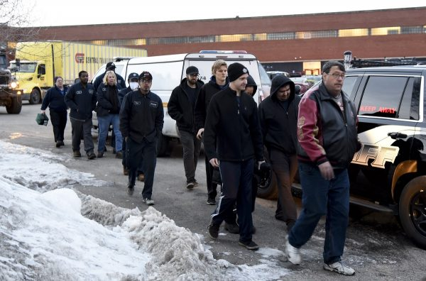 Employees are escorted from the scene of a shooting at a manufacturing plant