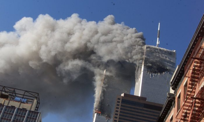 Smoke rises from the burning twin towers of the World Trade Center after hijacked planes crashed into the towers, in New York City on Sept. 11, 2001. (Richard Drew/AP)