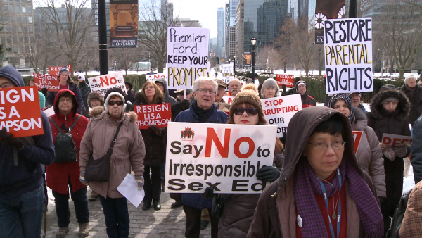 Protestors outside Queens Park demand Minister of Education Lisa Thompson step down in Toronto, Canada on Feb. 20, 2019. (NTD Television)