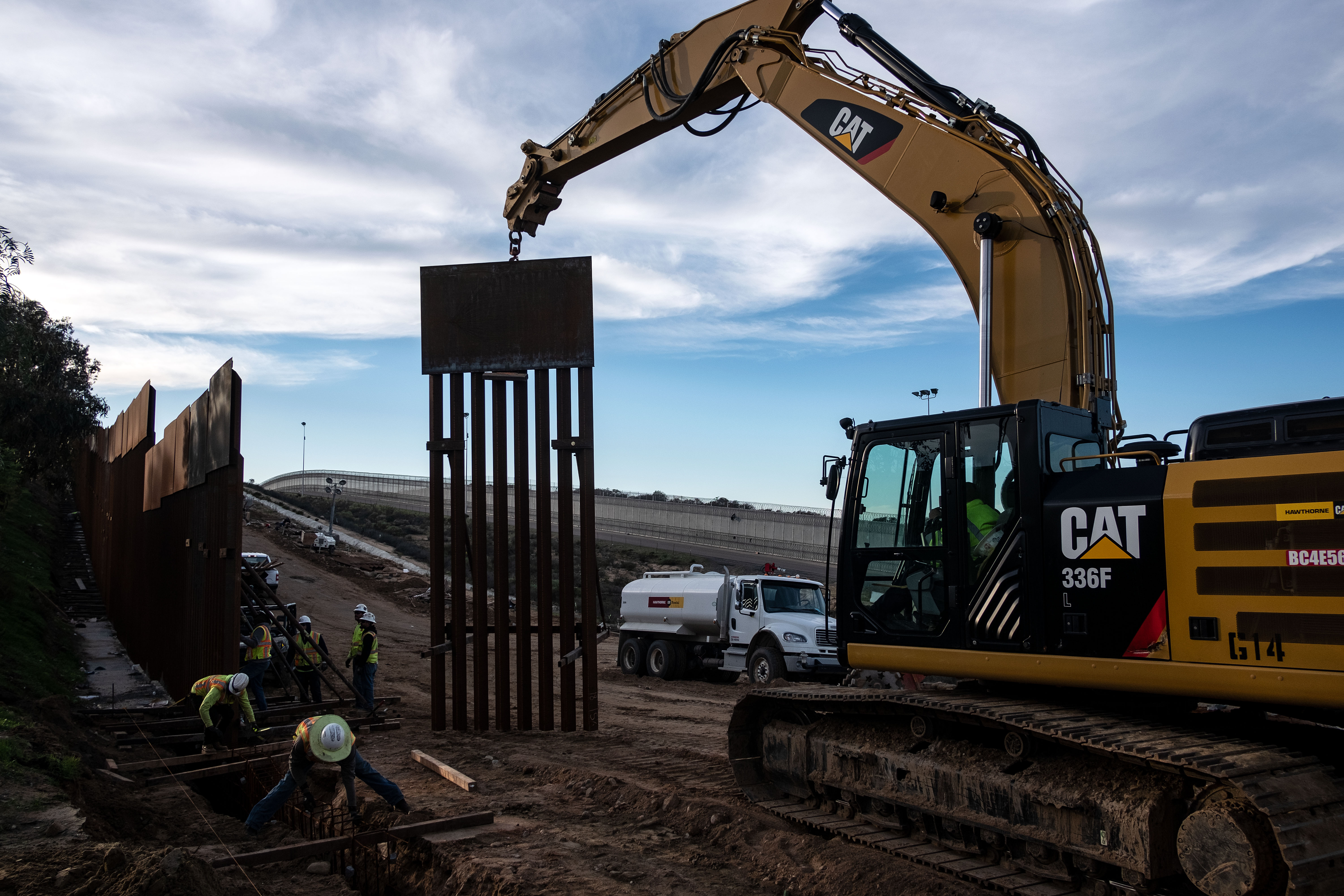 A construction crew works on replacing the U.S.-Mexico border fence as seen from Tijuana