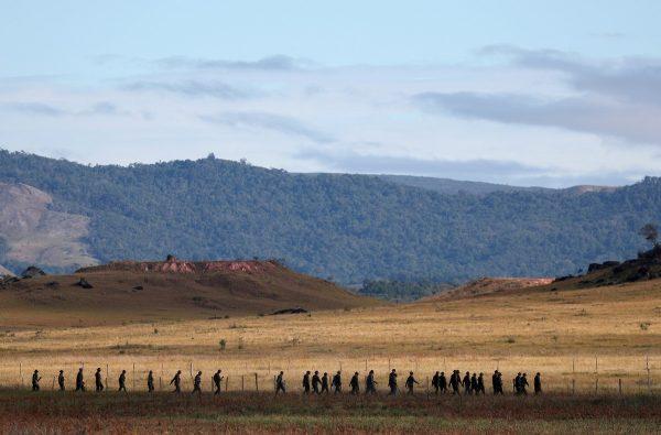Venezuelan soldiers walk at the border