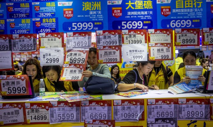 "People check on travel packages offered by travel agencies during the Guangzhou International Travel Fair in Guangzhou in south China's Guangdong Province on March 3, 2018. Travelers in China were blocked from buying plane tickets 17.5 million times in 2018 as a penalty for failing to pay fines or other offenses, the Chinese regime reported this week on penalties imposed under a controversial ""social credit"" system. (Chinatopix via AP)"