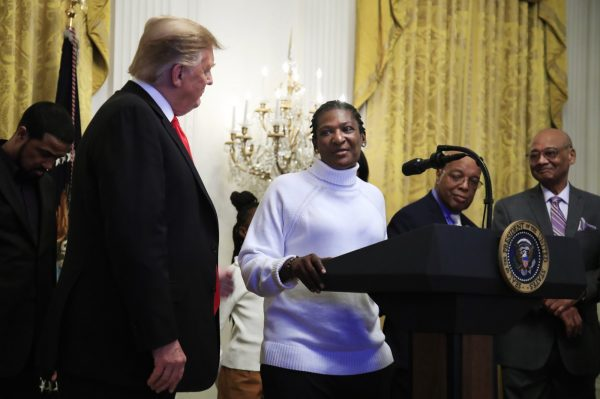 President Donald Trump listens to Catherine Toney speak during a National African American History Month reception