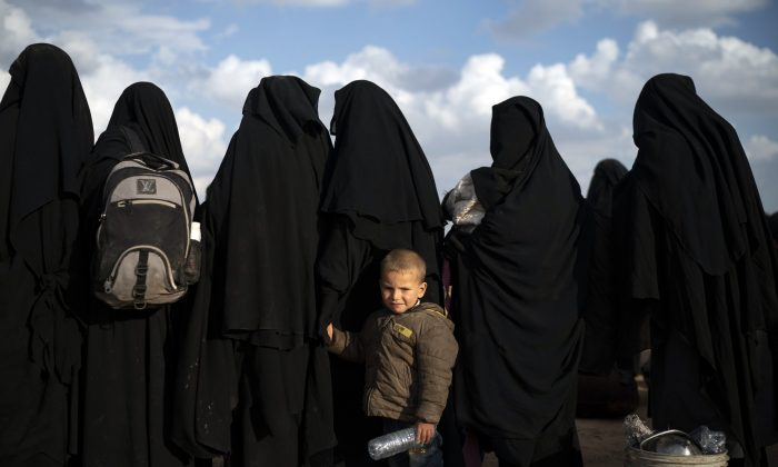 A boy holds her mother's hand as they wait to be screened after being evacuated out of the last territory held by ISIS terrorists, near Baghouz, eastern Syria, on Feb. 22, 2019. (Felipe Dana/AP Photo)