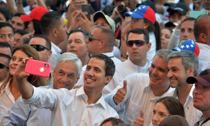 """Venezuela's opposition leader Juan Guaido (C) takes a selfie his wife Fabiana Rosales (R, foreground), Chilean President Sebastian Pinera (next to him at left), Colombian President Ivan Duque (2-R, giving thumb up), and Paraguayan President Mario Abdo Benitez (R) during the """"Venezuela Aid Live"""" concert in Cucuta, Colombia, on Feb. 22, 2019. (Luis Robayo/AFP/Getty Images)"""