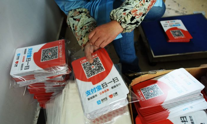 A worker packs newly printed cards showing Alipay QR codes for online payment at a printing factory in Hangzhou in China's eastern Zhejiang Province on July 16, 2018. (AFP/Getty Images)