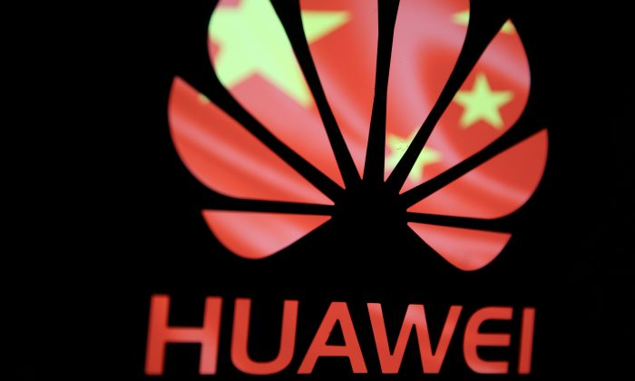 A Huawei logo in front of the Chinese Communist Party flag. National security experts warn of the security risks associated with Huawei in a panel event on March 21, 2019. (Dado Ruvic/Reuters)