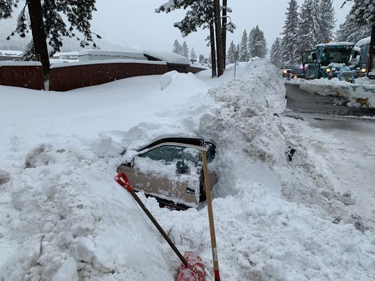 car buried in snow with woman inside