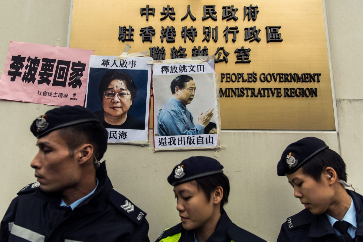 Police walk past missing person notices of Gui Minghai and Yau Wentian