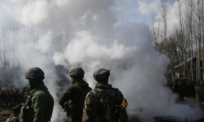 Indian army soldiers stand near the wreckage of an Indian helicopter after it crashed in Budgam area, outskirts of Srinagar, Indian controlled Kashmir, Wednesday, Feb.27, 2019.  (AP Photo/Mukhtar Khan)