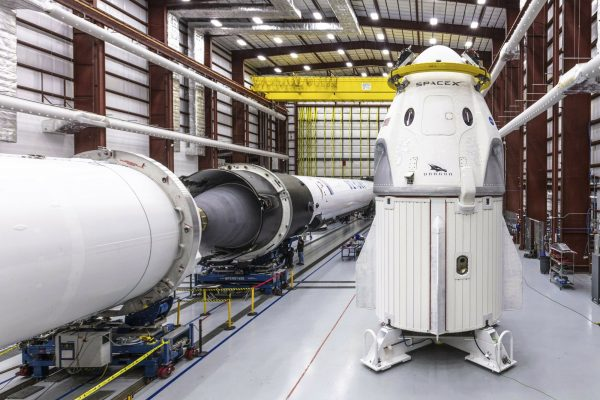 SpaceX's Crew Dragon spacecraft and Falcon 9 rocket are positioned inside the company's hangar