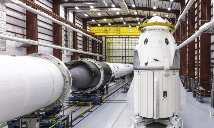 SpaceX's Crew Dragon spacecraft and Falcon 9 rocket are positioned inside the company's hangar at Launch Complex 39A at NASA's Kennedy Space Center in Florida, on Dec. 18, 2018. (Space X via AP)
