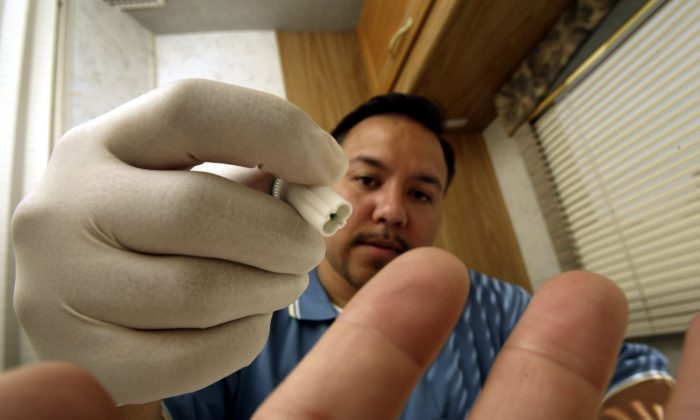 Joe Mendoza, AIDS Healthcare Foundation (AHF) mobile testing program manager, uses the photographer's finger to demonstrate how a lancet from the OraQuick Rapid HIV-1 Antibody Test kit would be used to obtain a blood sample inside the AHF mobile HIV screening lab on its first day of operations in Los Angeles, Calif. on Apr. 28, 2004. (David McNew/Getty Images)