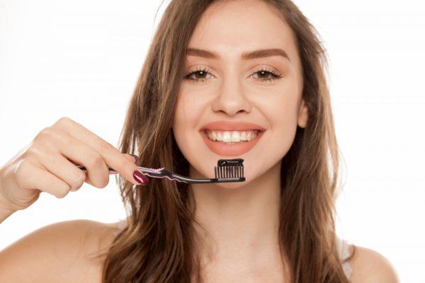 girl brush teeth with charcoal