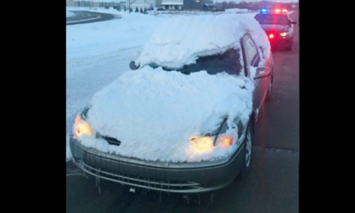 The Minnesota State Patrol tweeted a photo of a car that got pulled over recently for being almost entirely covered in snow, save for a small square of the windshield in front of the driver and the driver's door window. (Minnesota State Police)