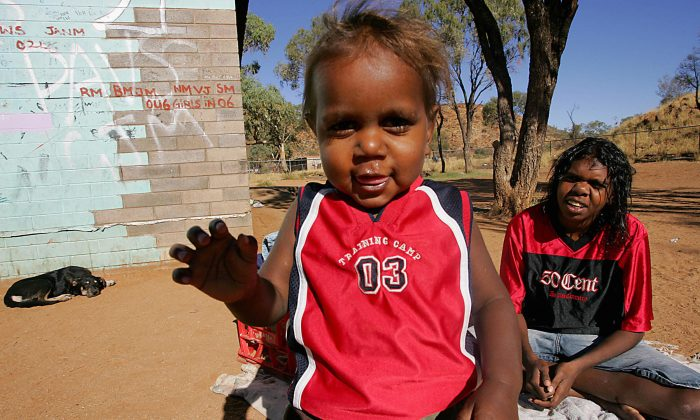 """Aboriginal 1 year old child Willy (L) and sister Lucia (R) play at the family's house in camp 'Hidden Valley' which is one of the """"town camps"""" around Alice Springs on May 18, 2007. (ANOEK DE GROOT/AFP/Getty Images)"""