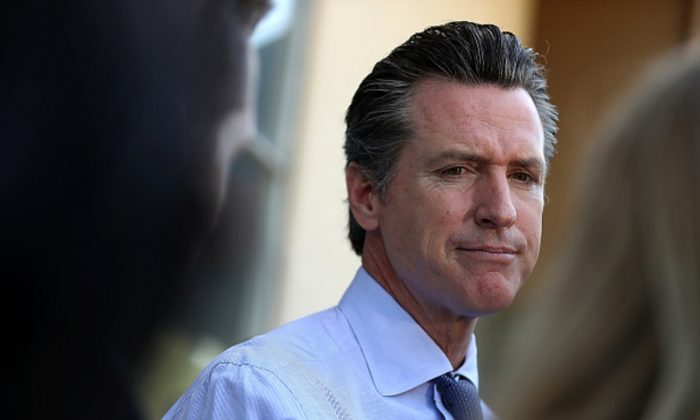 Democratic California Gov. Gavin Newsom (R) talks with reporters after voting at the Masonic Temple Fairfax in Larkspur, California, on June 5, 2018. (Justin Sullivan/Getty Images)