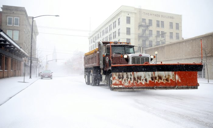 A snow plow rumbles north on Capitol Avenue during a blizzard in Casper, Wyo., on March 13, 2019. (Jacob Byk/The Wyoming Tribune Eagle via AP)
